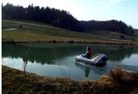 a kid is flying real hovercraft over the water